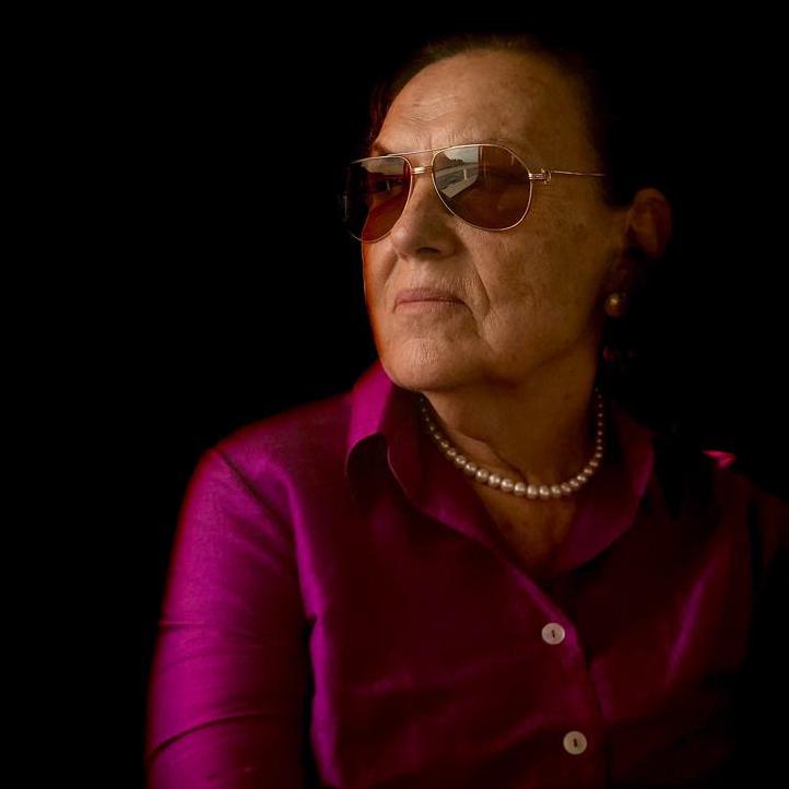 Πορτρέτο της Μπεράλ Μαντρά. Έχει σκούρα μαλλιά πιασμένα σε κότσο και φορά γυαλιά βιολετί μεταξωτό πουκάμισο και μαργαριτάρια. Ποζάρει προφίλ και κοιτά σκεπτική.