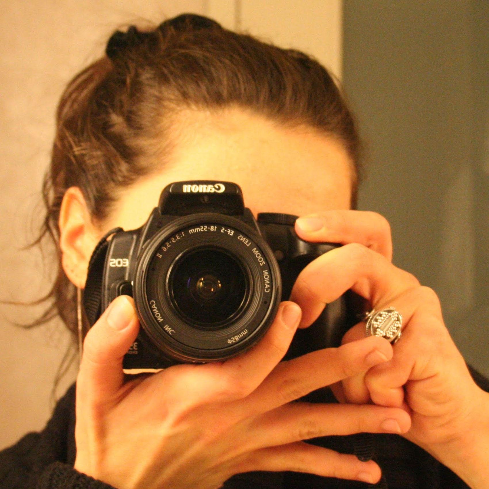 Καλλιτεχνικό πορτρέτο της Χαράς Ιωάννου. Έχει καστανά μαλλι΄πιασμένα σε αλογοουρά και φορά μαύρο πουλόβερ. Το πρόσωπό της κρύβεται από τη φωτογραφική της μηχανή (Canon) την οποία κρατά με τα δυο της χέρια. Φορά λαμπερό δαχτυλίδι.
