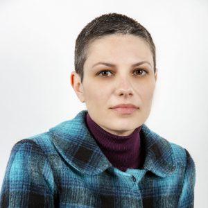 Πορτρέτο της Ελένης Σπετσιώτη. Έχει πολύ κοντά γκρίζα μαλλιά και φορά μωβ πουλόβερ και μαύρο και τουρκουάζ καρό σακάκι. Κοιτά ευθέως.