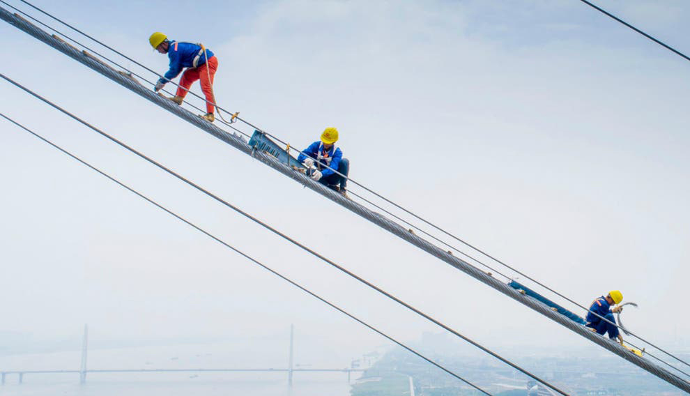Three construction workers working in a high altitude, in great risk