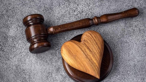 Gavel and wooden heart on concrete gray background. Family law concept