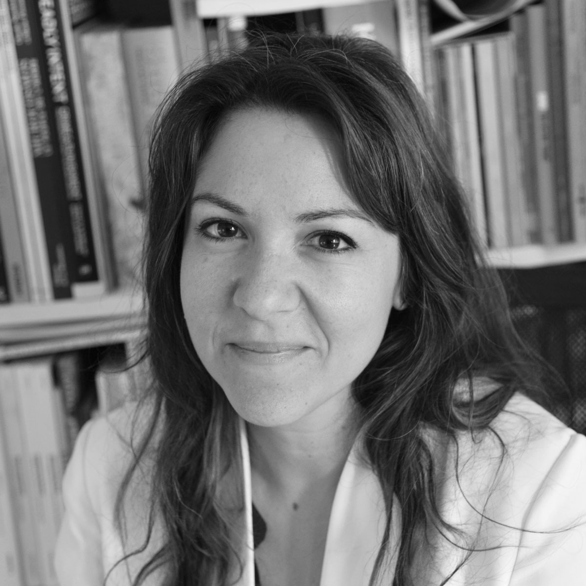 Ασπρόμαυρο πορτρέτο της Ηλιάνας Φωκιανάκη. Έχει μακριά μαύρα μαλλιά και καστανά μάτια. Φορά άσπρο πουκάμισο, κοιτά το φακό και χαμογελά. Ποζάρει μπροστά σε μια βιβλιοθήκη.