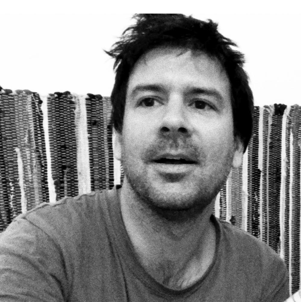 Ασπρόμαυρο πορτρέτο του Γιώργου Μουστάκη. Έχει κοντά, καστανά μαλλιά.Φορά Τι-σερτ. Κοιτάζει ψηλά στο πλάι.