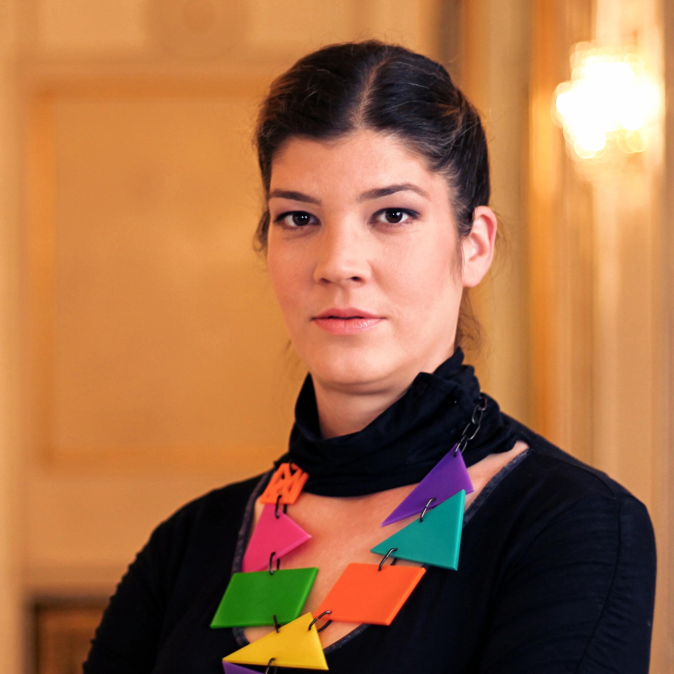 Πορτρέτο της Ιβάνα Νενάντοβιτς. Έχει σκούρα καστανά μαλλιά σε αλογοουρά. Φορά μαύρη μπλούζα και περίτεχνο κολιέ με μεγάλα πολύχρωμα τρίγωνα. Κοιτά ευθέως.