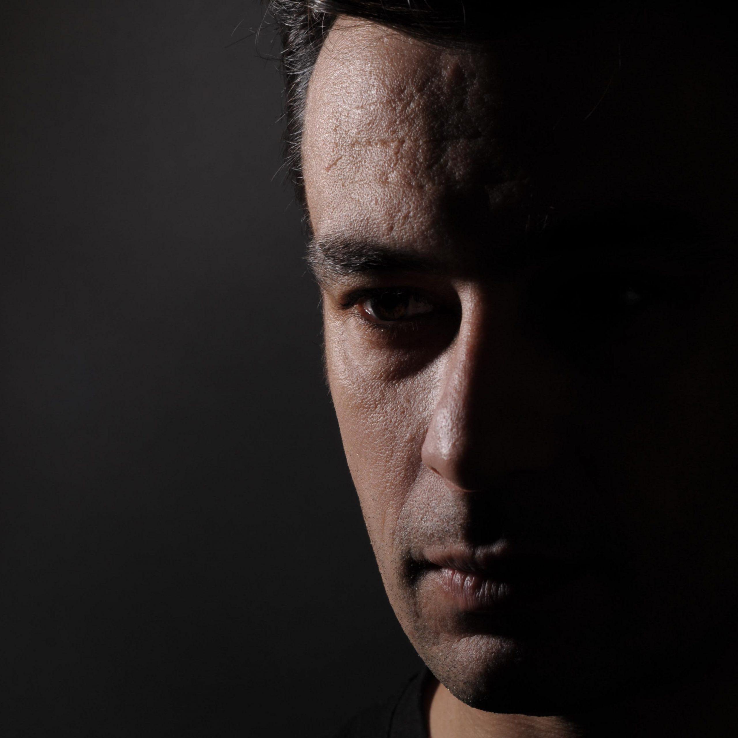 Πορτρέτο του Δημήτρη Ζωγραφάκη. Έχει μαύρα κοντά μαλλιά και μαύρα μάτια. Φορά μαύρο τισέρτ. Το μισό πρόσωπο βρίσκεται στη σκιά και κοιτάζει στο πλάι.
